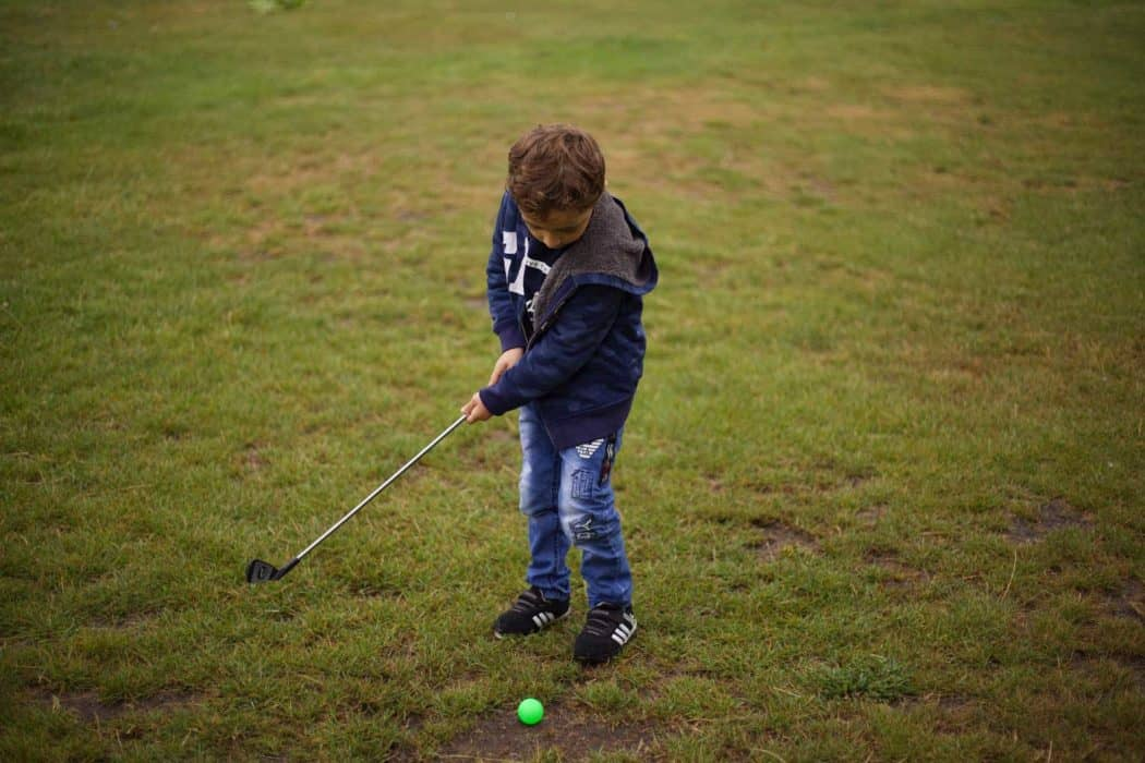 young boy putting on a golf course