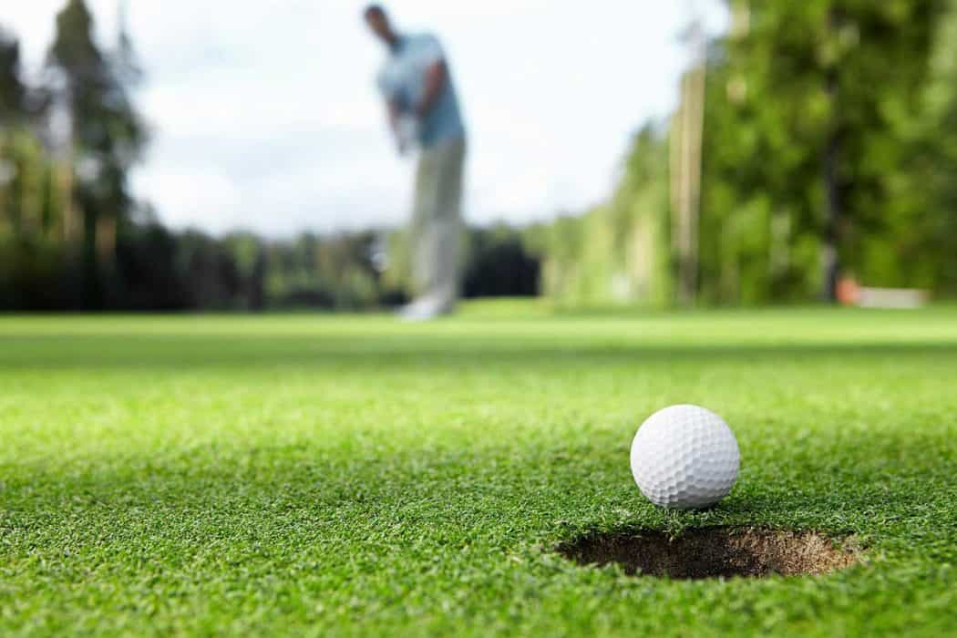 golf ball being putted into the hole