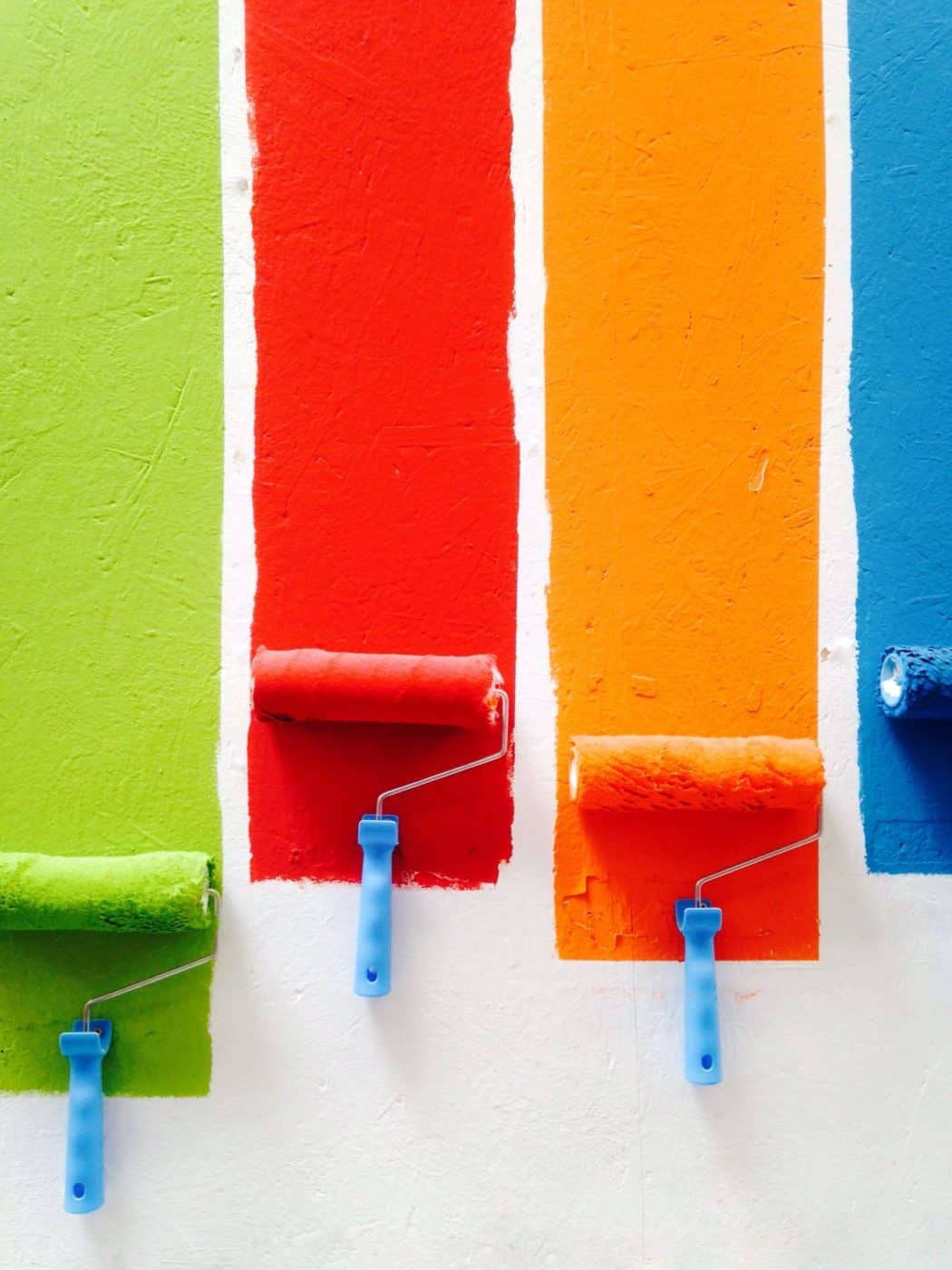 multiple colored paint rollers on a wall painting a room